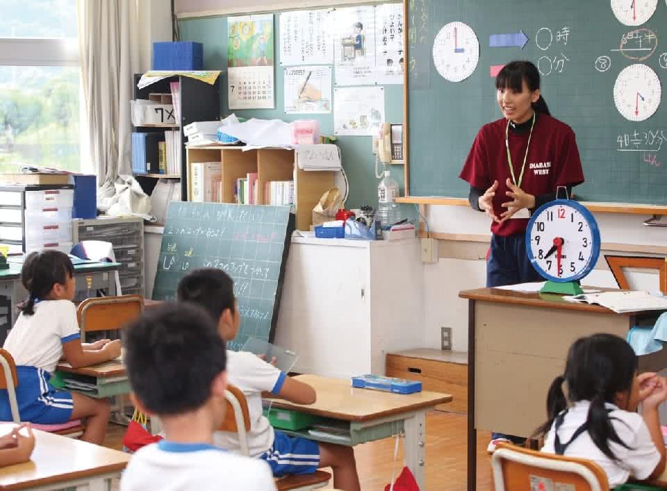 写真:女性が教室で教材の時計を使って授業をしている様子