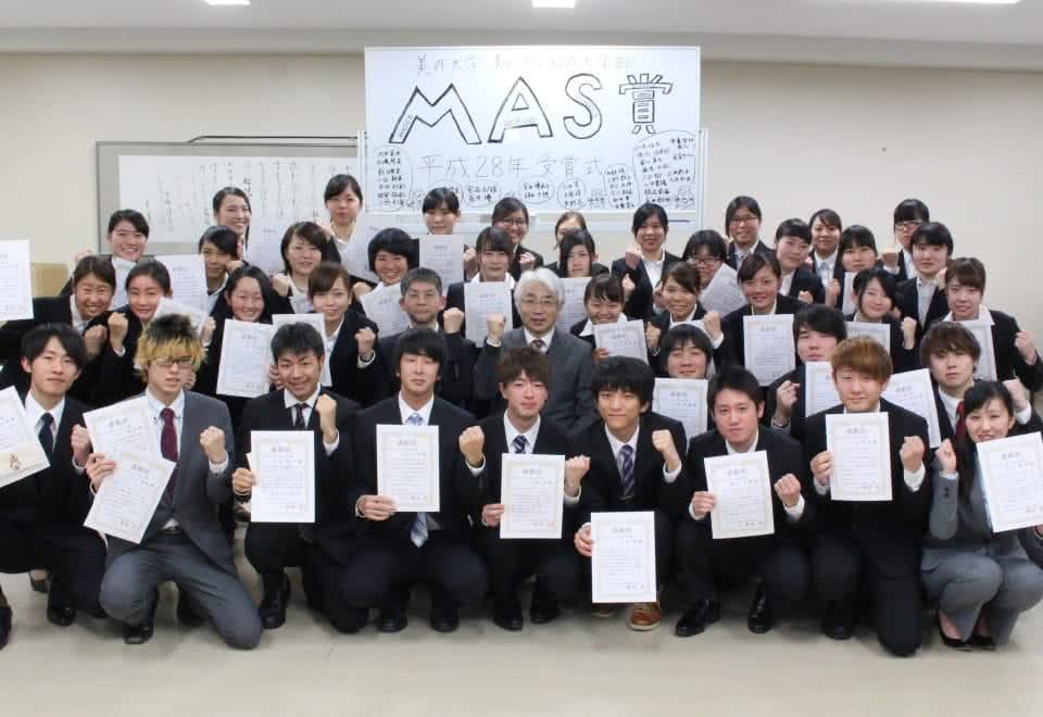 写真:MAS賞と書かれたホワイトボードの前でスーツを着て賞状を持ち、ガッツポーズで集合した学生たちと、その中央にいる学長