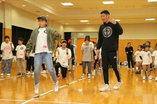 写真:体育館でリズムジャンプに挑戦する大勢の小学生と、指導する津田准教授