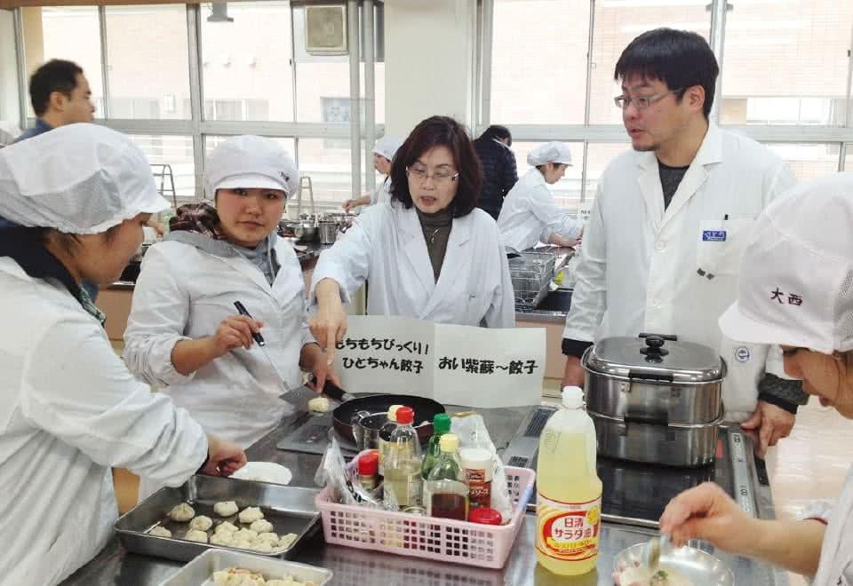 写真:白衣を着て調理室で津山餃子を開発中のつやま夢みのりグループのメンバーたち