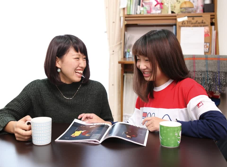 写真:指定アパートで友達と雑誌を読むAさん