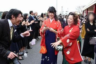 写真:笑顔で卒業生を指差す教員と、笑顔で駆け寄る卒業生