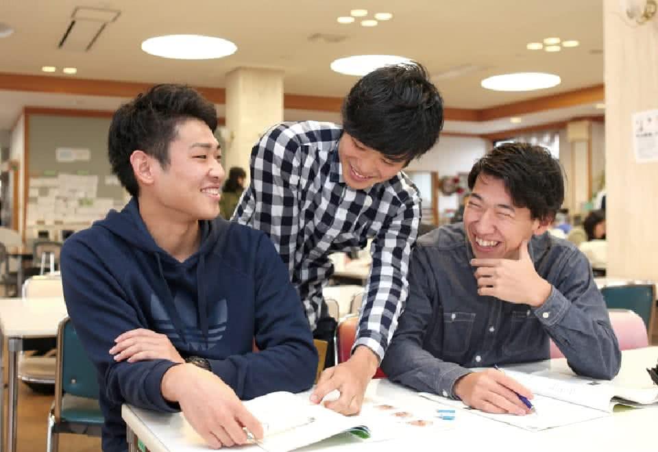 写真:学生ホールで友だち二人と教科書やノートを広げて試験対策をするBさん