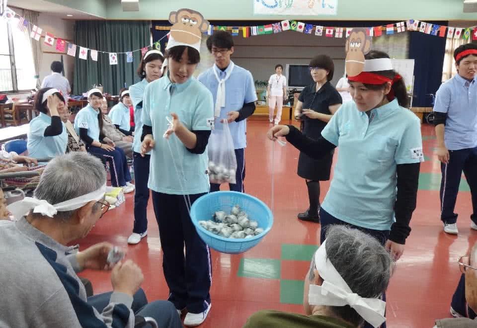 写真:高齢者施設で実習生がお面をつけて利用者の方と接している様子
