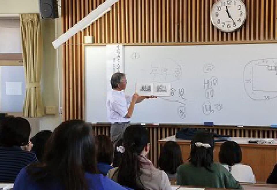 写真:講座にて絵本について講演する講師と、受講する参加者
