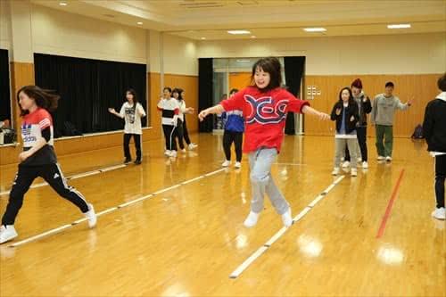 写真:体育館でラインの上をまたいだりジャンプしたりする学生