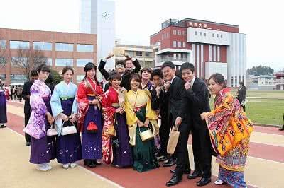 写真:校舎の前で集まってポーズをとる12名の卒業生