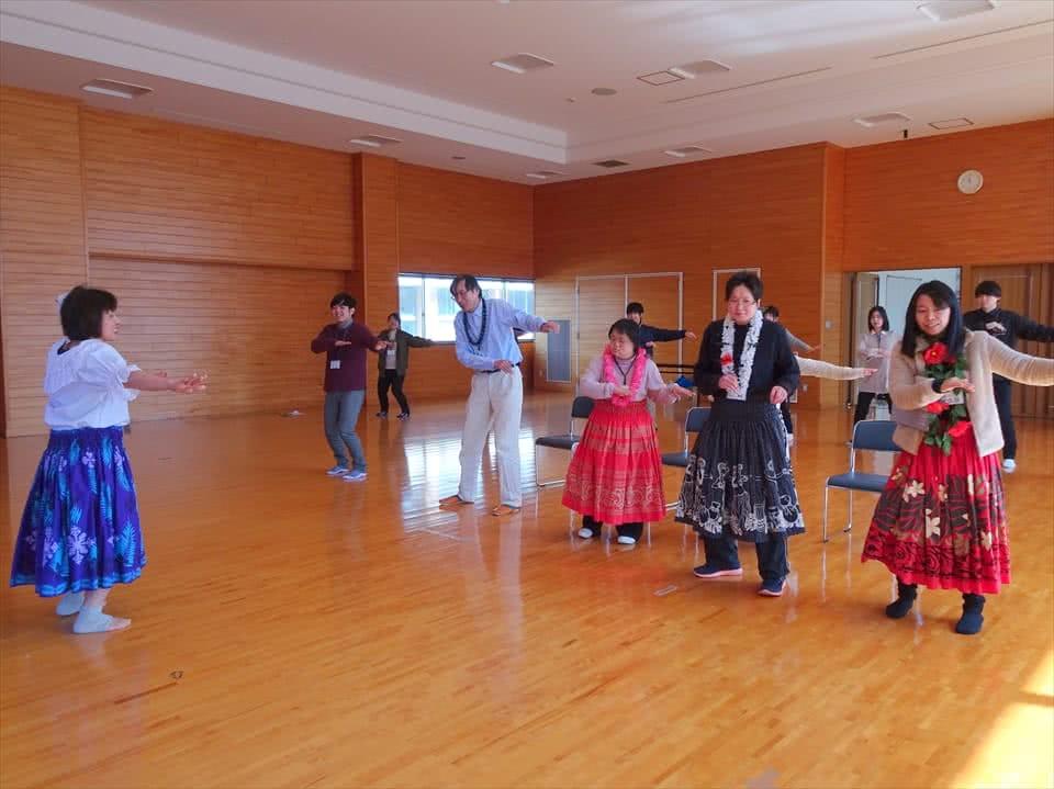 写真:カラフルな衣装を身にまとってフラダンスをする受講生と講師