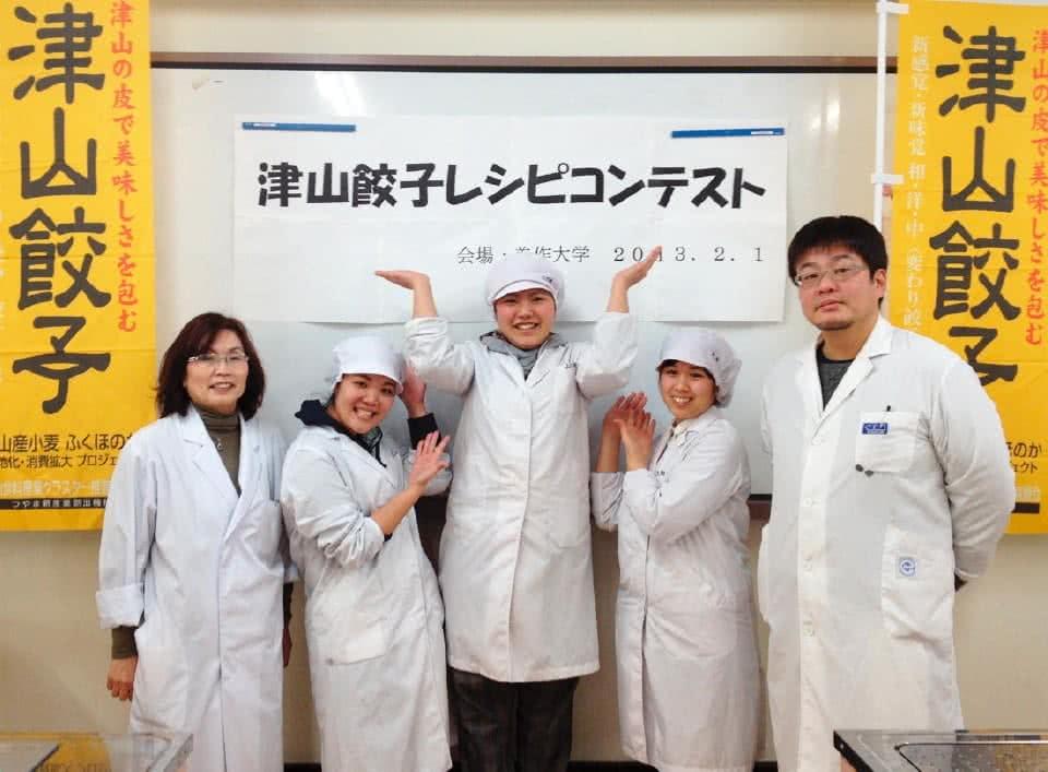 写真:「津山餃子」と書かれた旗を左右に、中央に「津山餃子レシピコンテスト」と書かれた紙が貼られたホワイトボードの前で白衣を着て並ぶつやま夢みのりグループの5人