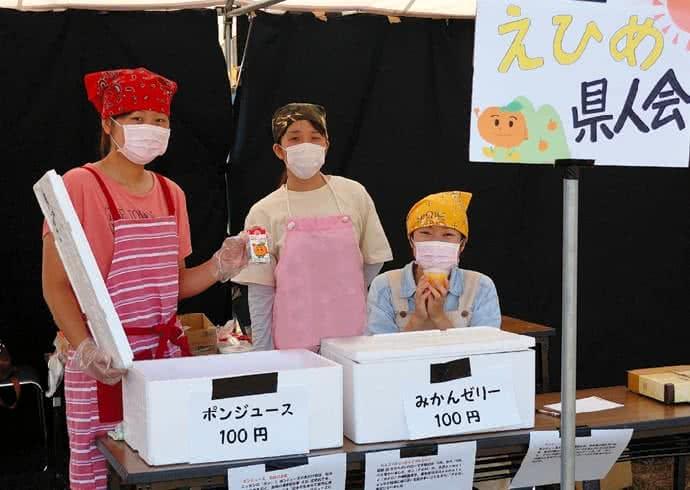 写真:エプロンと三角巾、マスクを付け、白梅祭でポンジュースとみかんゼリーを100円で販売する愛媛県人会の3人のメンバー