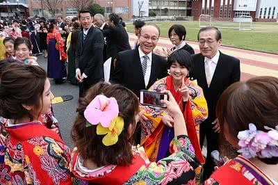 写真:教員2名と一緒に写真をとる学生。