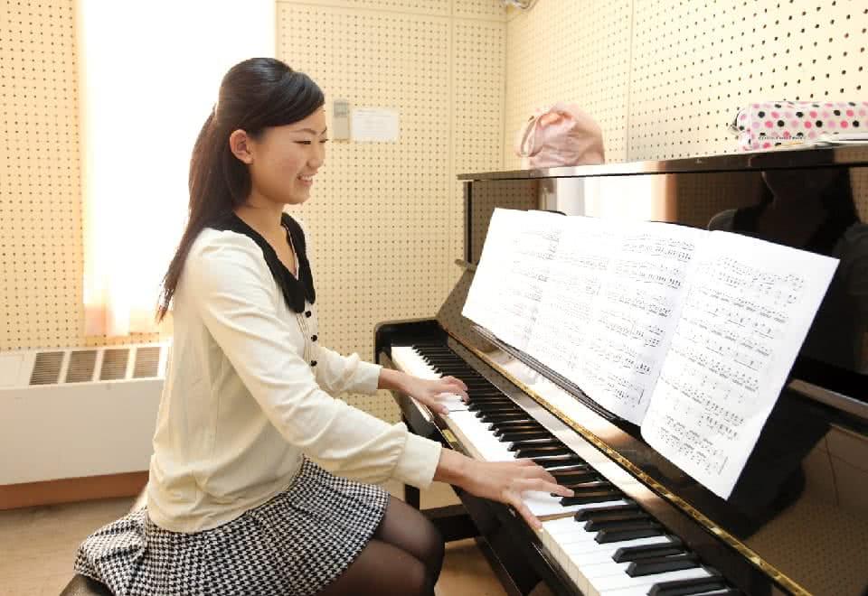 写真:女性がピアノを練習している様子