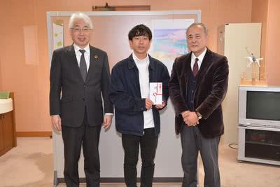 立正佼成会 津山教会長の東伸吉様から寄付金を受け取る学生