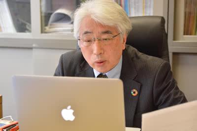 ノートパソコンを使ってオンライン公園を行う鵜﨑学長