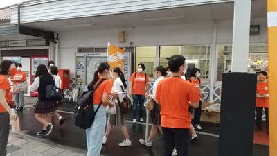 JR津山駅前で高校生へパンフレットを渡す様子